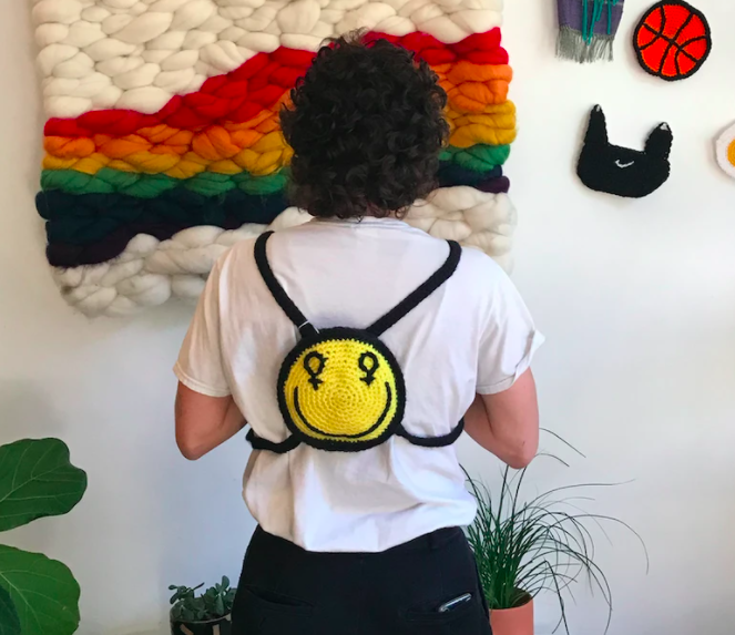 Model wears smiley crocheted mini backpack on their back