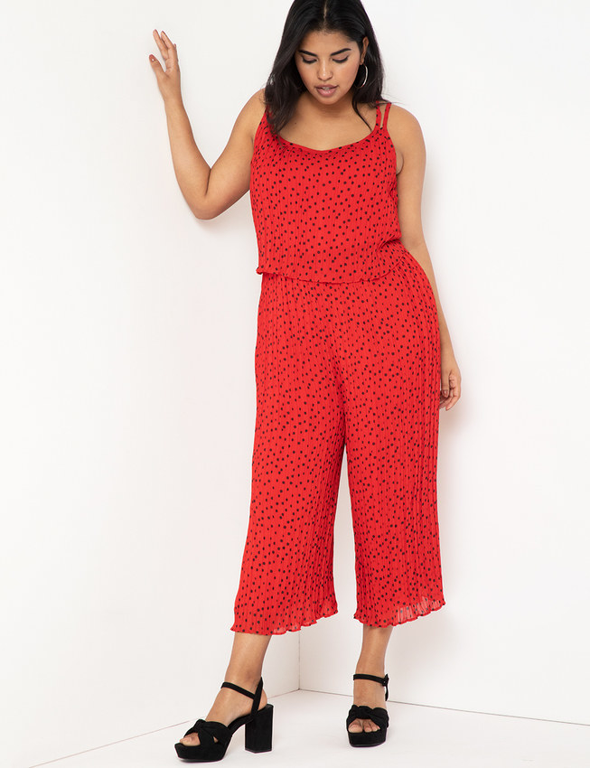 a model wearing a red jumpsuit with black tiny polka dots