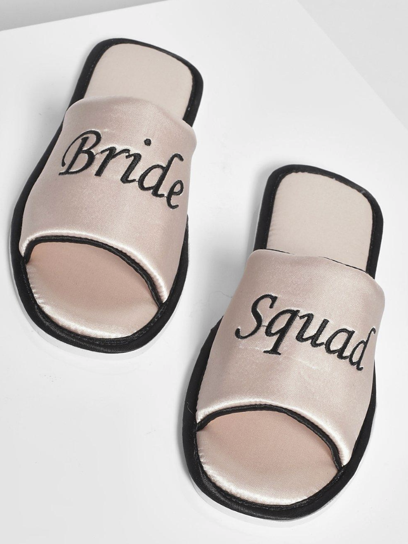 "Open-toe slippers with black trim that and satin-like material that says ""Bride"" on one shoe and ""Squad"" on the other"