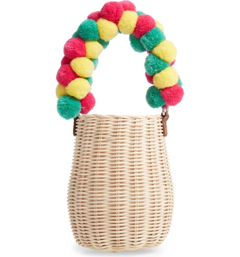 woven basket style bucket bag with bright pom pom covered handle