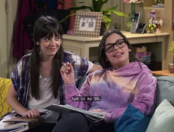 Elena and Syd do homework together on the couch while explaining their relationship to others on the show.