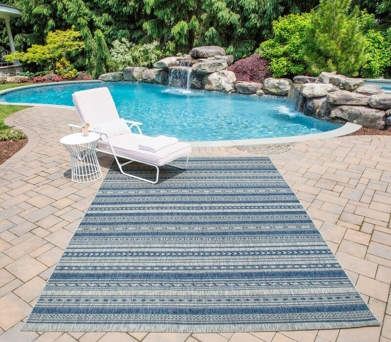 The rug in blue outdoors by a pool