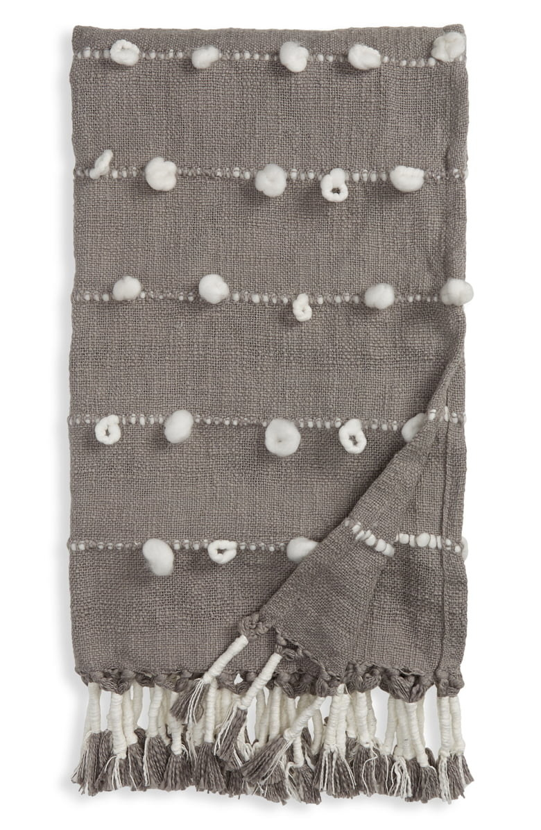 gray and white blanket with tassels on edge and irregular pom poms on it