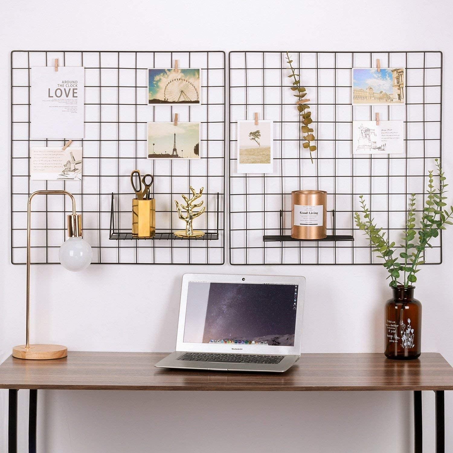 A wired frame is mounted on a wall with notes and pictures attached to it above a desk with a laptop on it