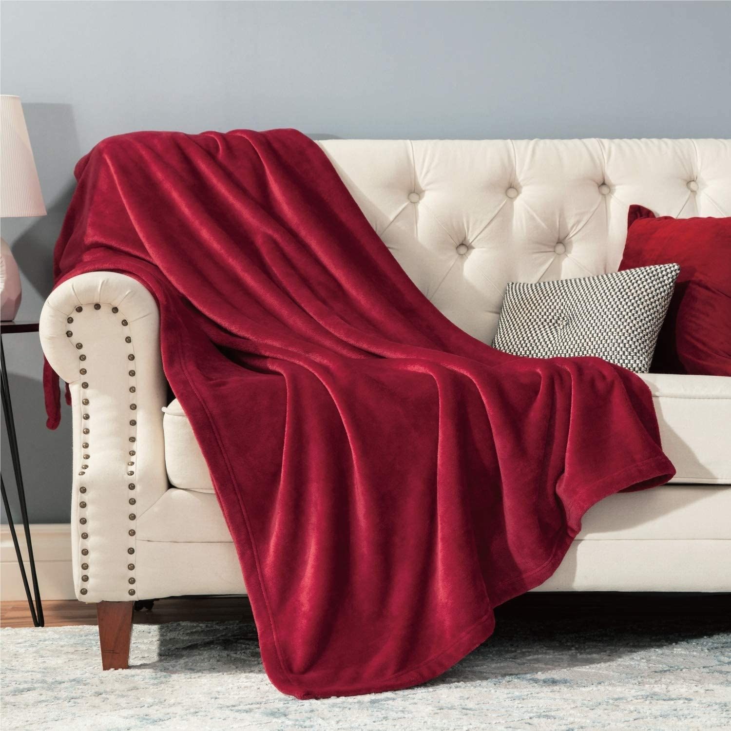 A fluffy throw is draped across a couch with pillows on it