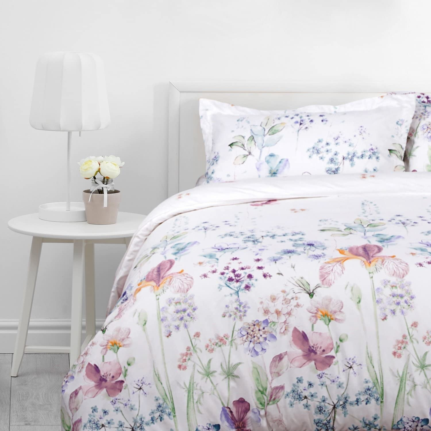 A floral duvet cover and pillowcases are on a bed