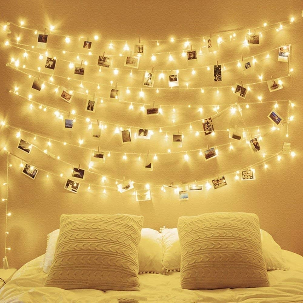 Fairy lights are strung up above a bed with pictures attached to the cord with clothespins
