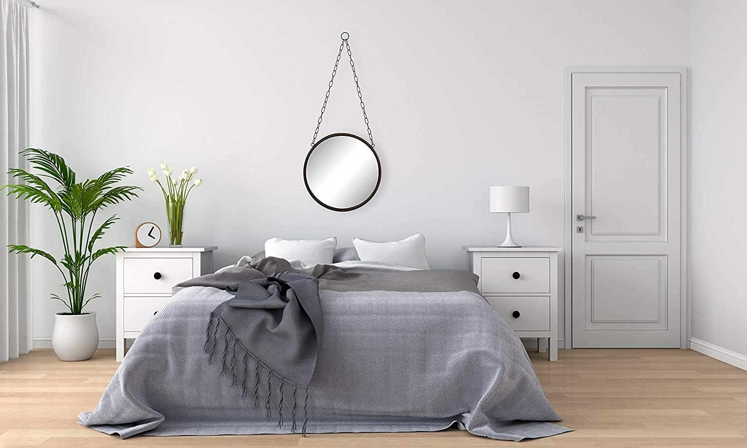 A round mirror with a chain hangs above a bed in a bedroom