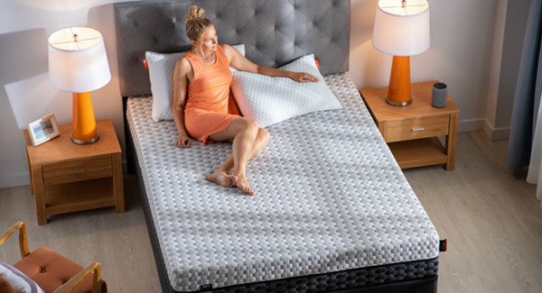 a model sitting on a memory foam mattress with two pillows