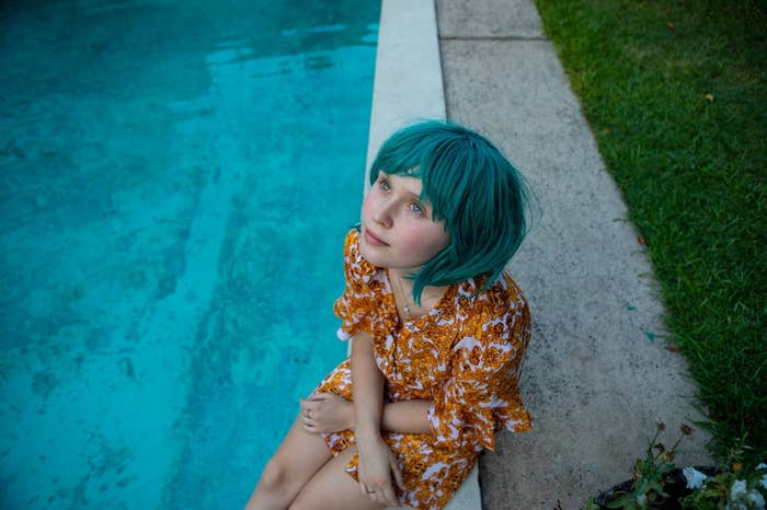 A teenage woman sits next to a pool, wearing a green wig.