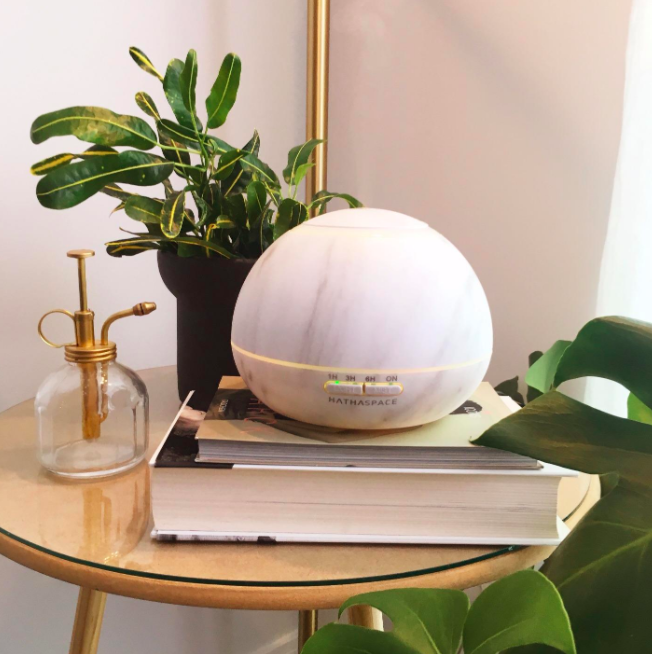 Orb-shaped marble-style diffuser sitting on end table