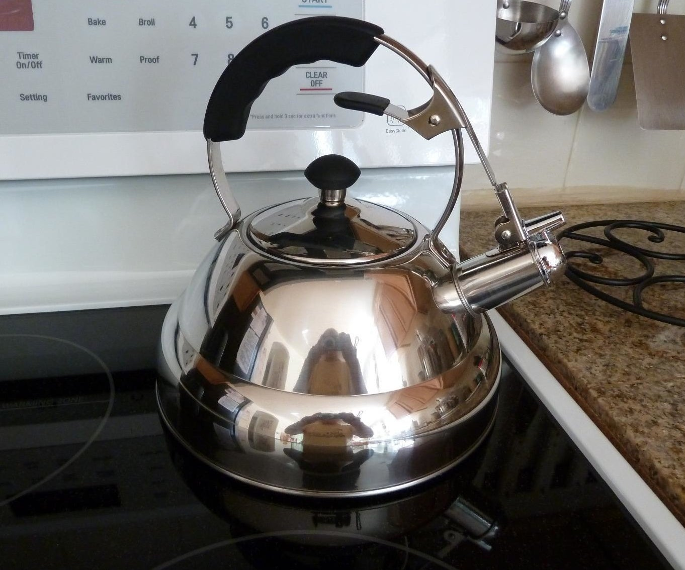 A reviewer's photo of a shiny metallic tea kettle sitting atop an electric range