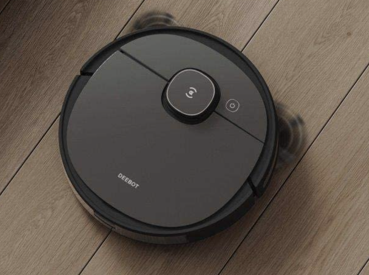 the circular robot vacuum cleaning a wood floor