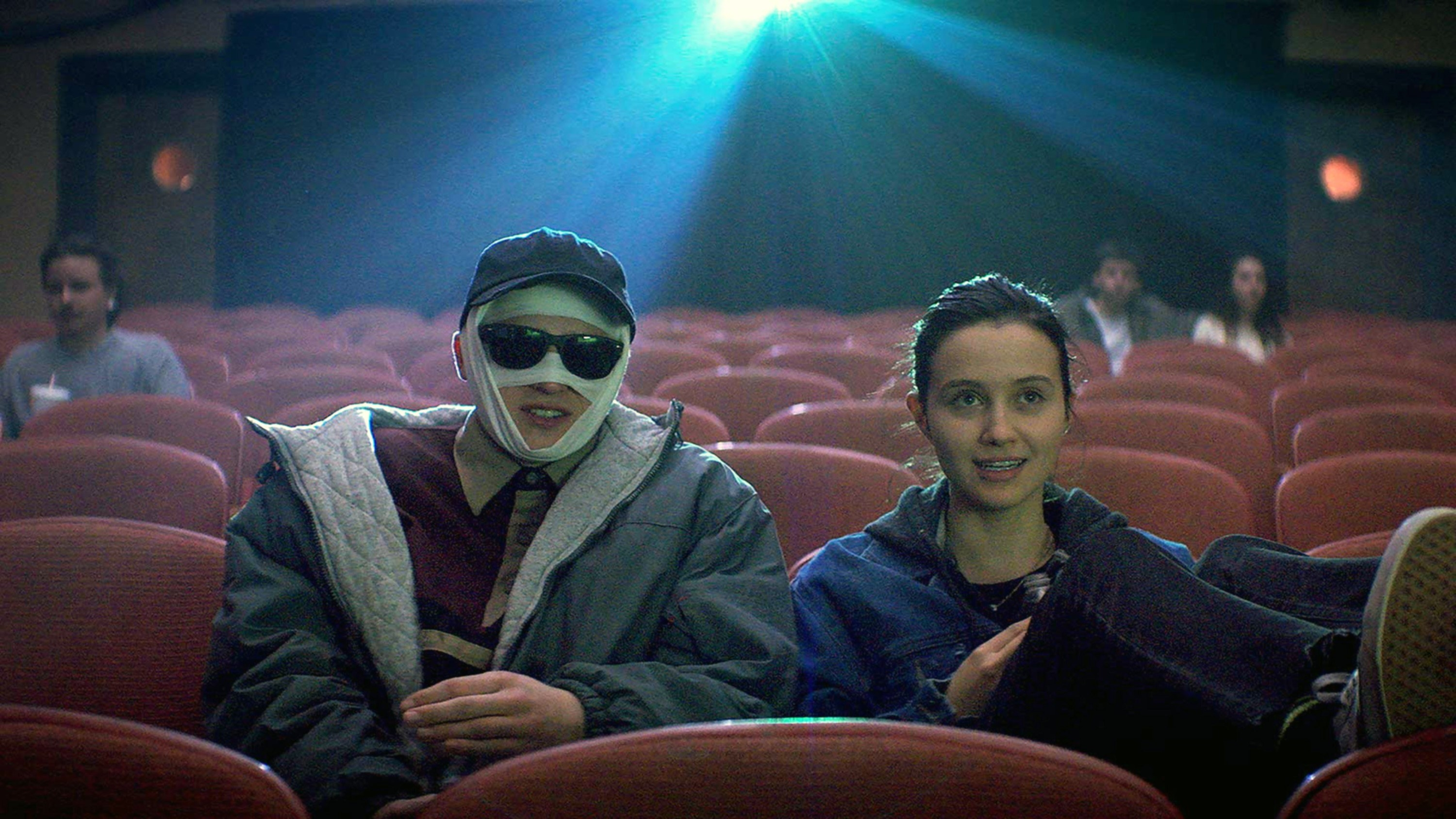 A man with bandages all over his face at the movies with a girl sitting next to him.
