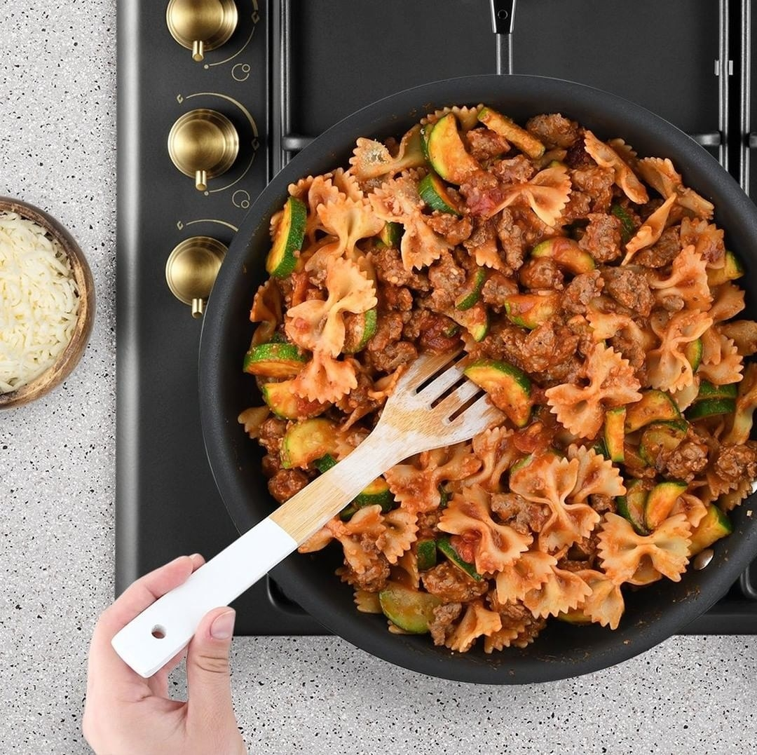 a hand stirring a full pot of bow tie pasta in sauce with meat and zucchini