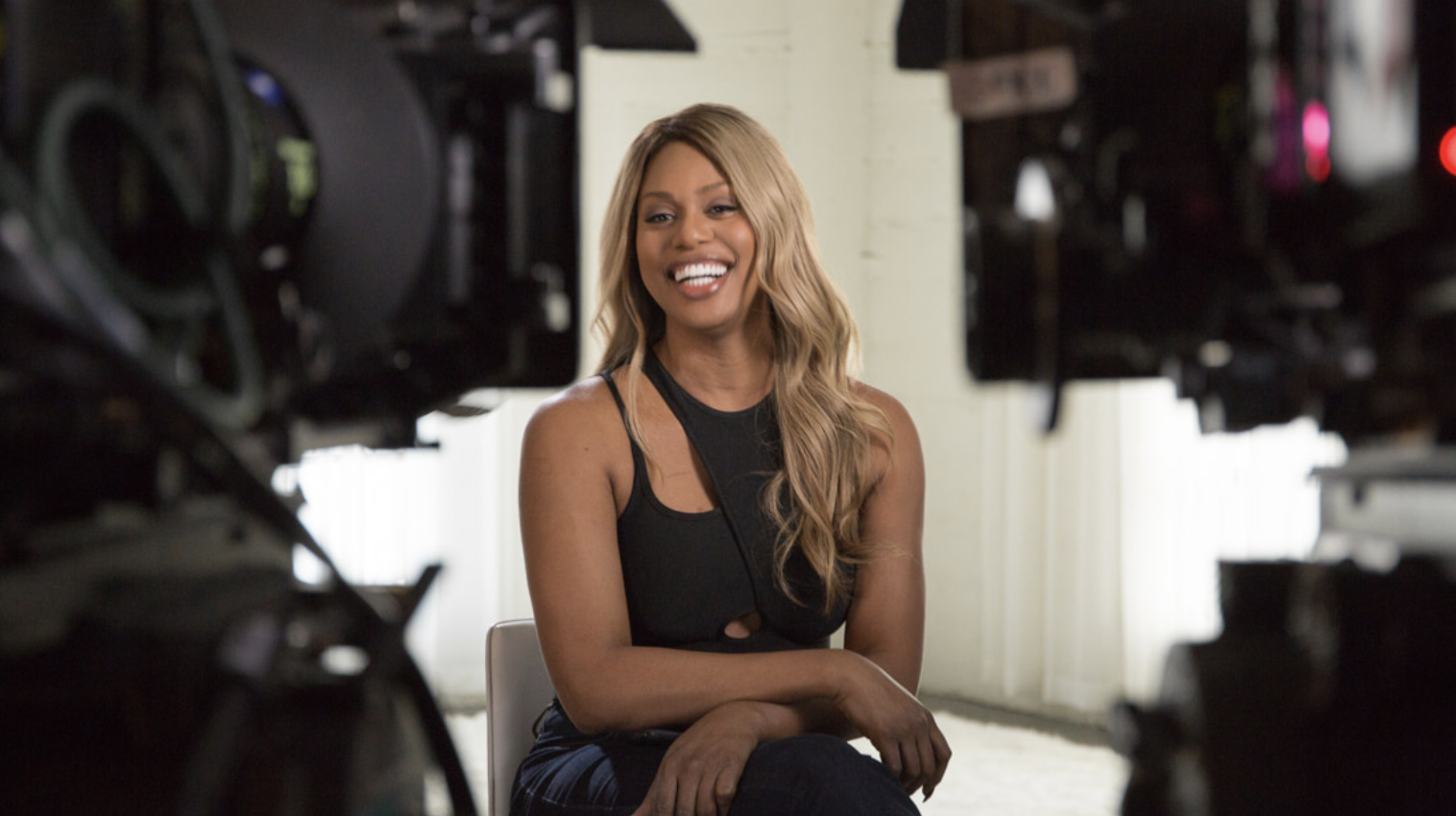 Laverne Cox is interviewed behind two cameras.