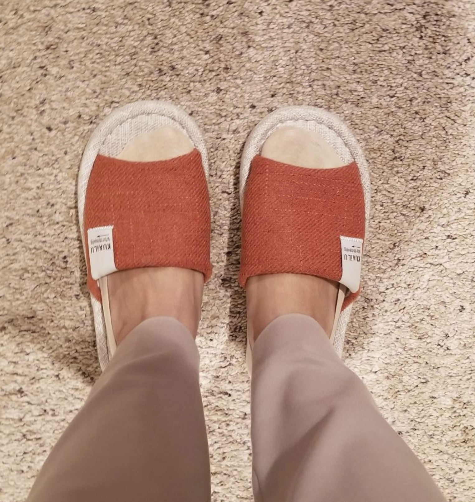 Reviewer's foot wearing the shoes with linen cloth on the top. They're dark orange.
