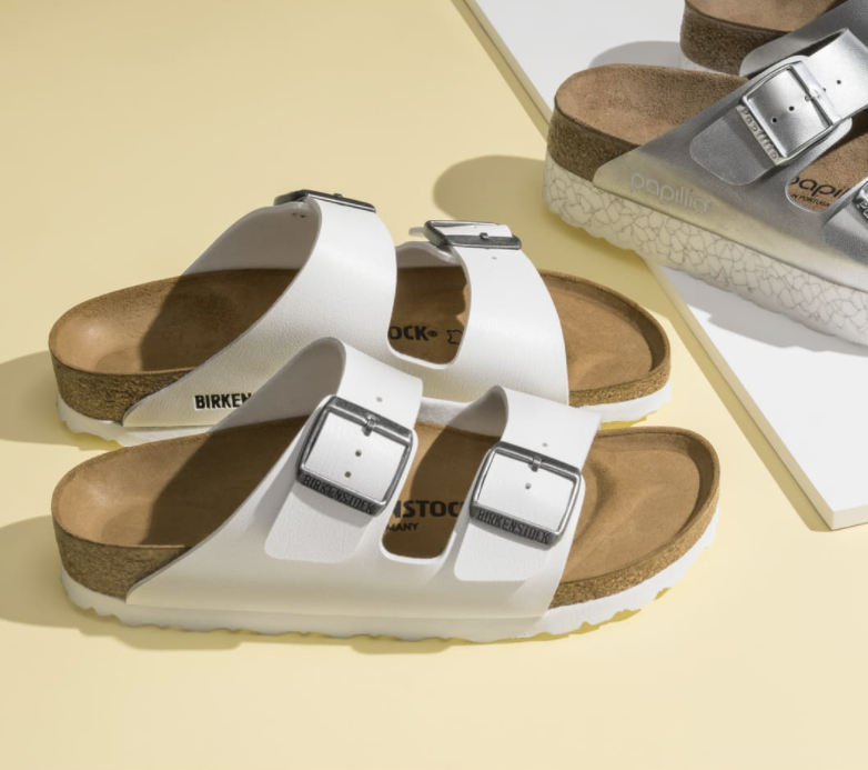The sandals in white with two big buckle straps across the top, a brown footbed and white sole
