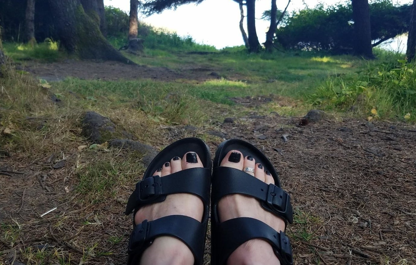 Reviewer wearing the sandals in black outside
