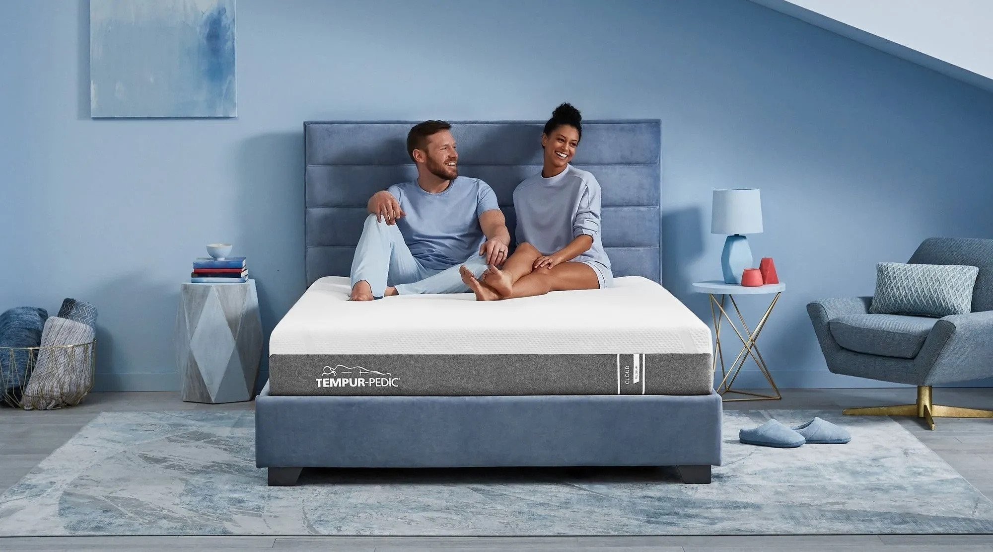 Two models sitting in a bad atop a Tempur-pedic mattress