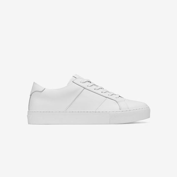 Side view of the sneakers in white showing the thick white stripe, heel, and laces