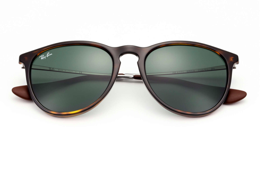 A pair of rounded Ray-Ban sunglasses sit folded on a plain background