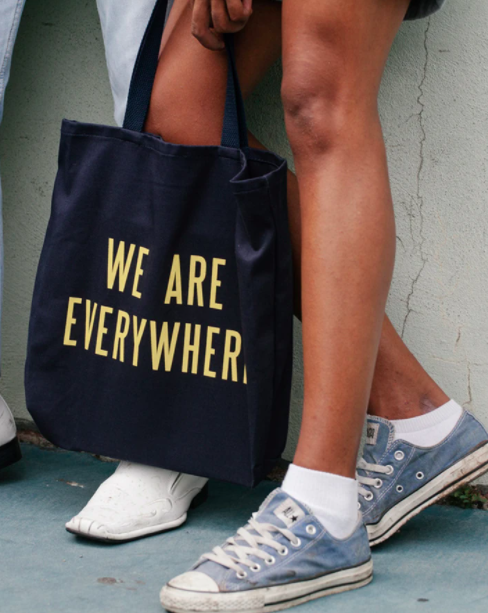 "Model carries black tote bag that says ""We Are Everywhere"" in yellow letters"
