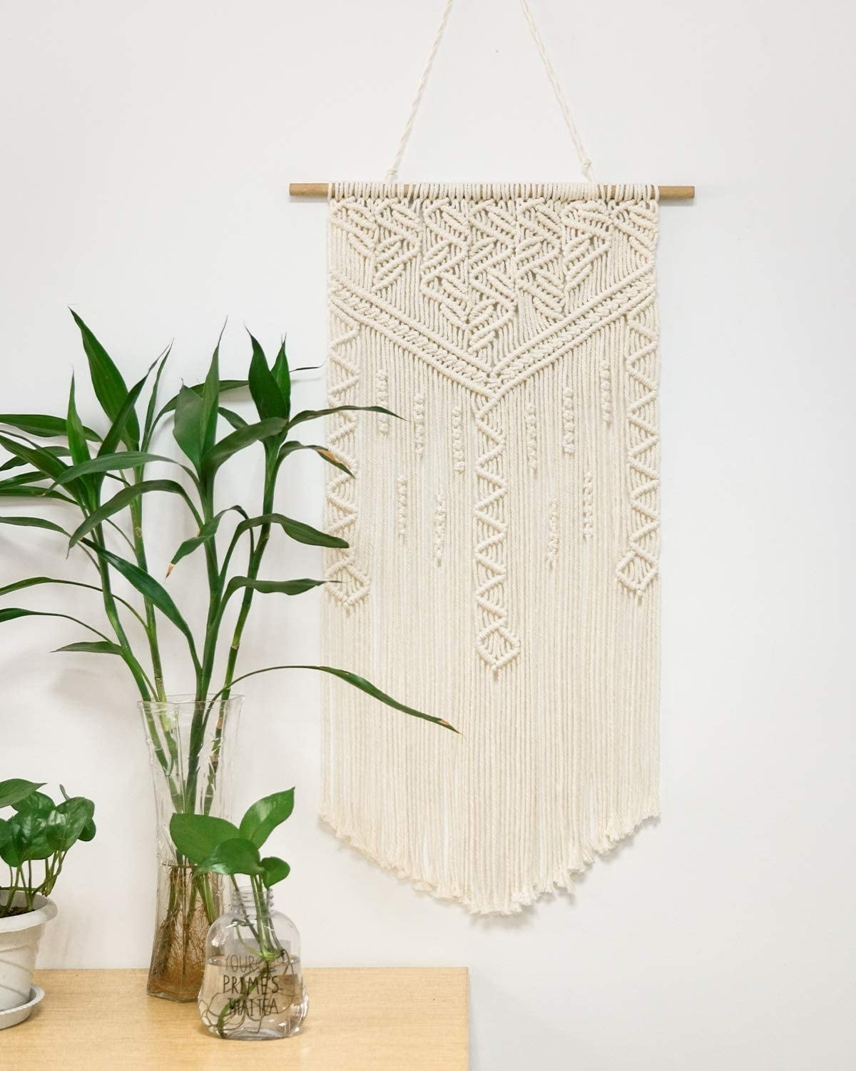 A macrame decoration hangs on a wall with dowel to support it and a hanging string