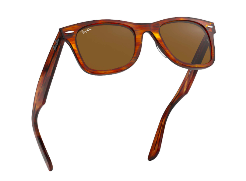 A pair of tortoiseshell Ray-Ban sunglasses in mid-air