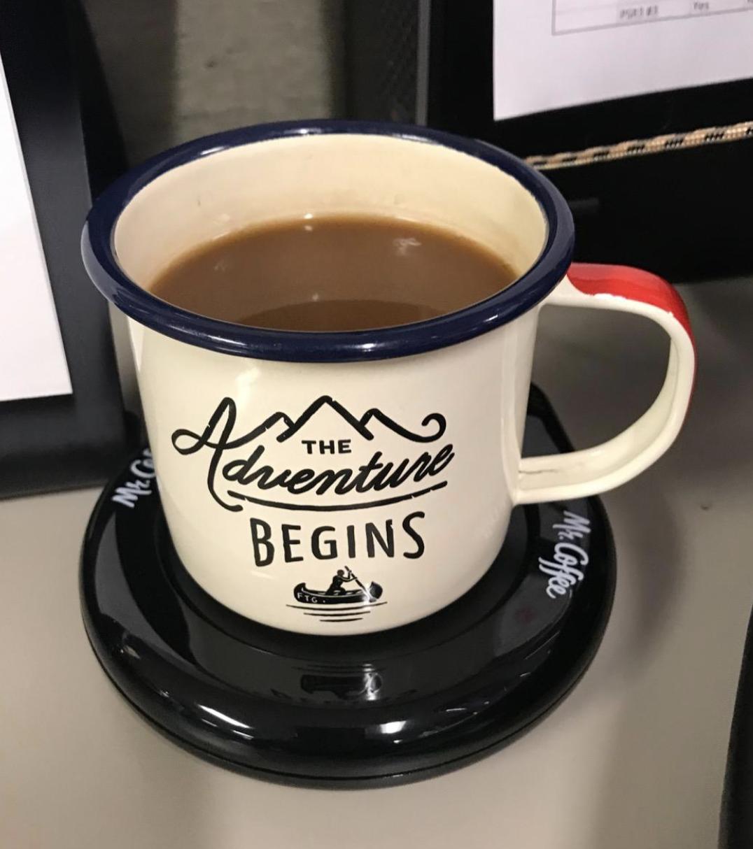 ceramic mug on the black coffee maker