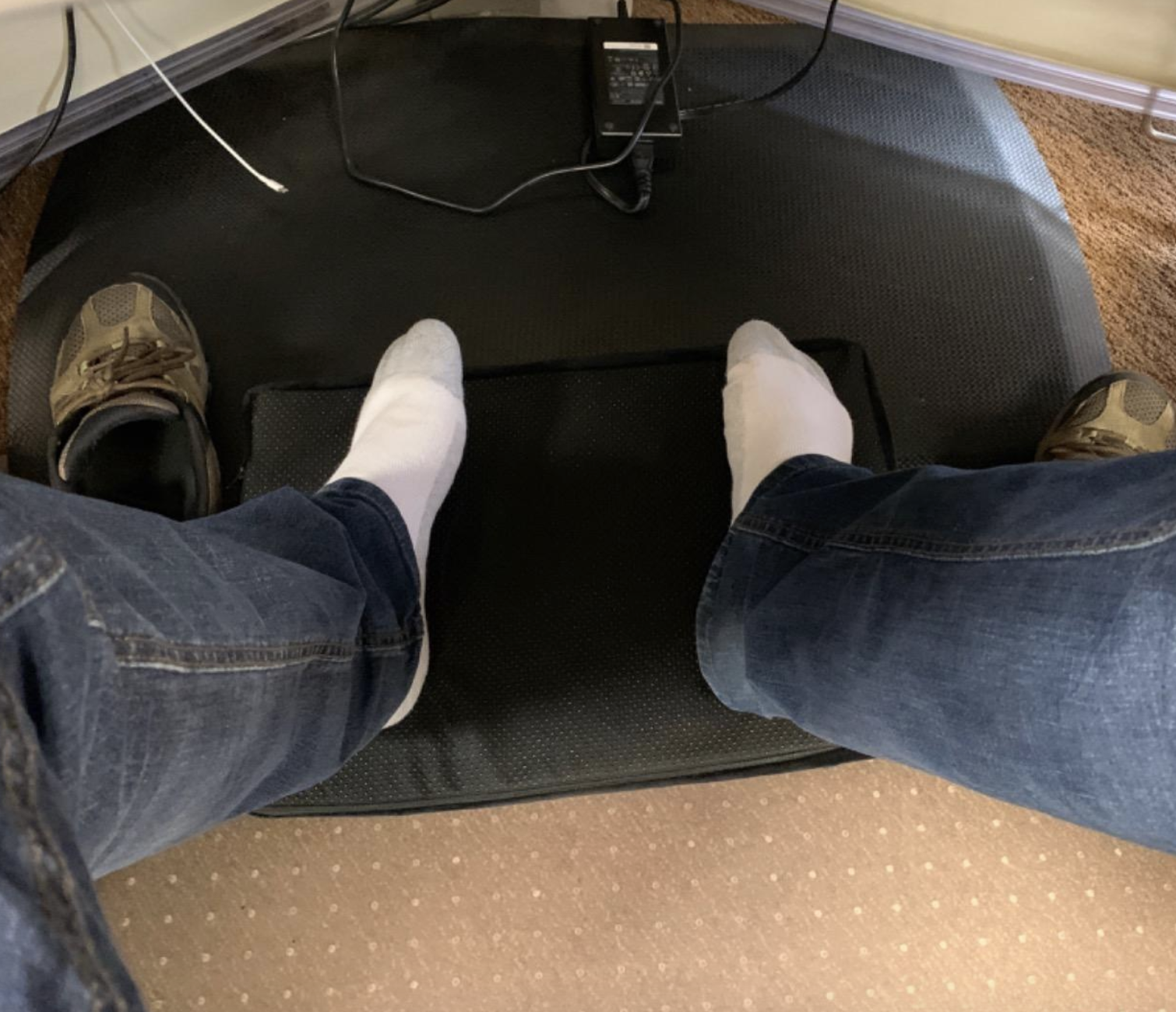 reviewer using black foot rest under desk