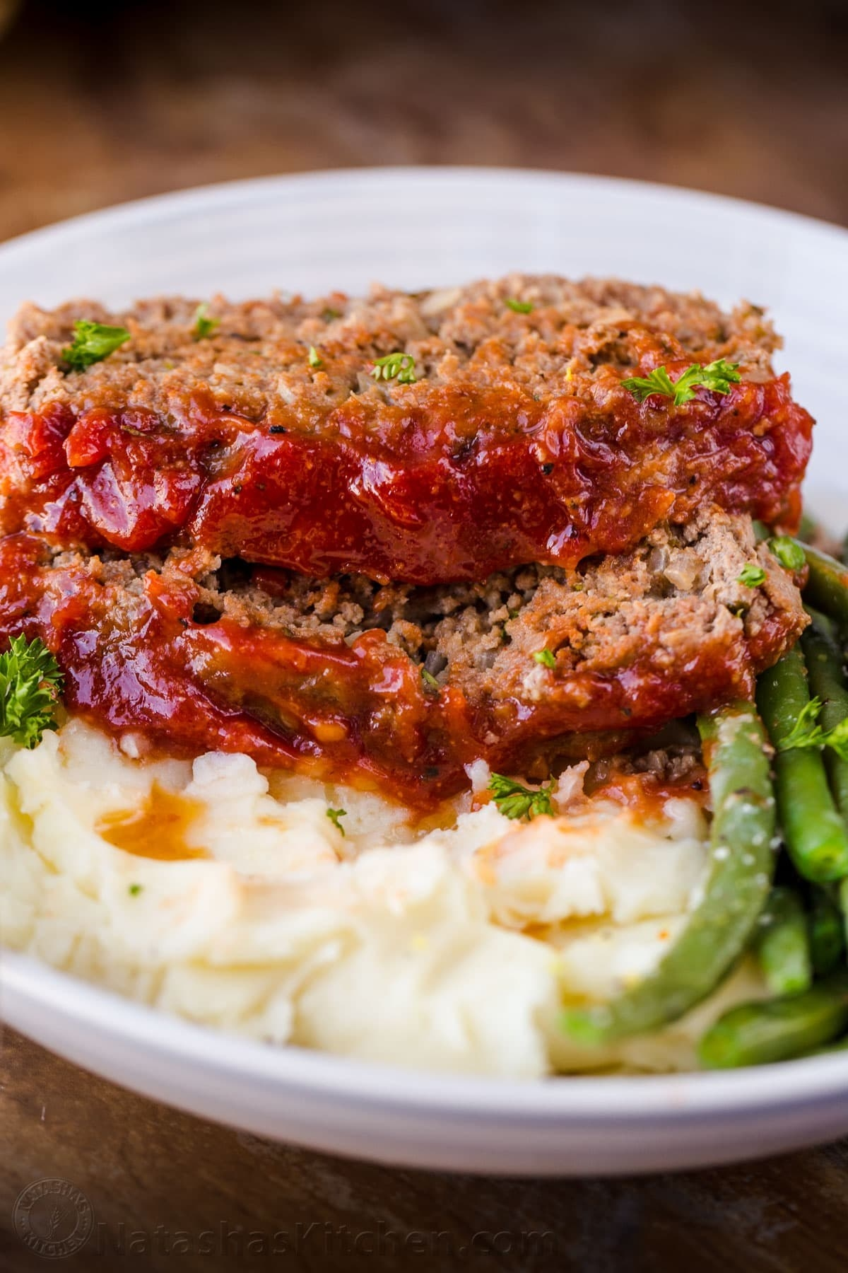 Two slices of meat loaf with ketchup on a bed of mashed potatoes with a side of bright green beans