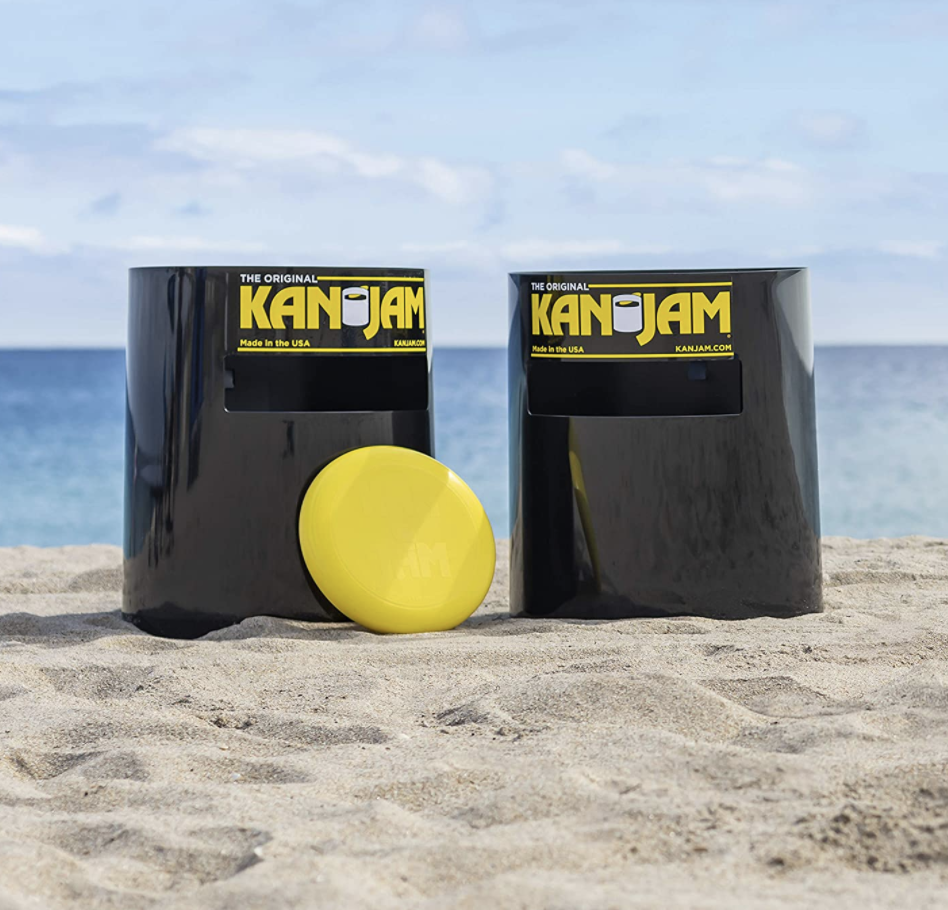 Two Kan Jam cans and a yellow frisbee on a beach