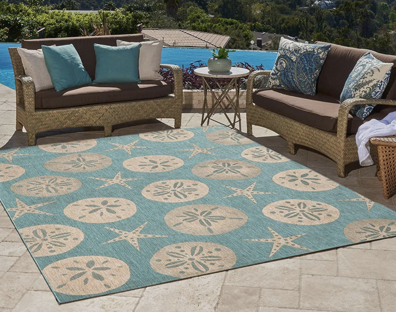 A starfish-patterned blue and nude rug placed next to patio furniture