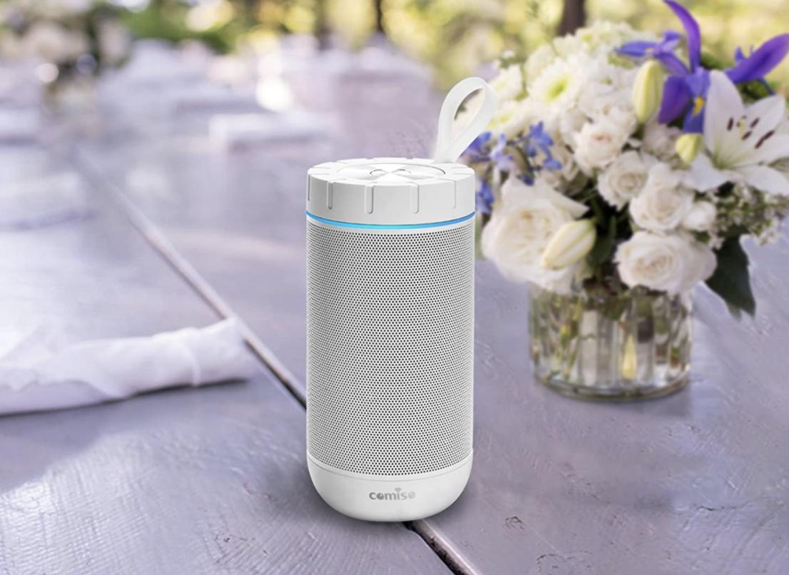 A white waterproof speaker on a purple picnic bench