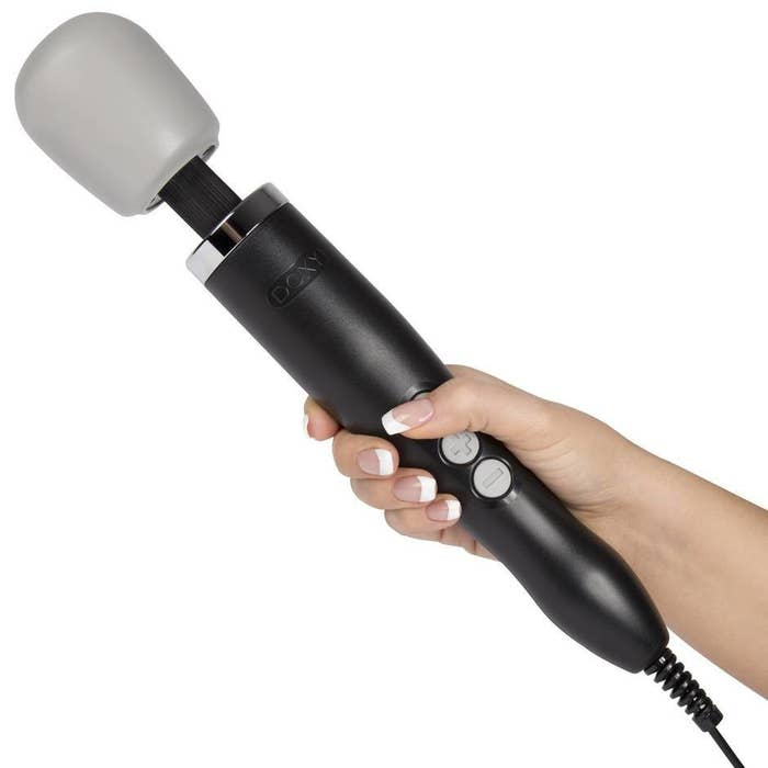 person holding the doxy wand massager with three large buttons visible