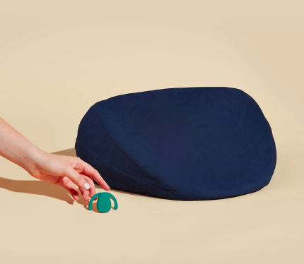 the same vibrator in green with a wedge shape pillow