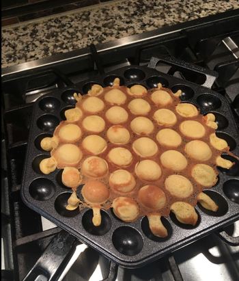 The pan, which has a series of little holes for putting batter in, with a partially cooked egg waffle in it