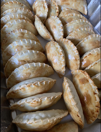 A row of perfectly cooked and identical empanadas