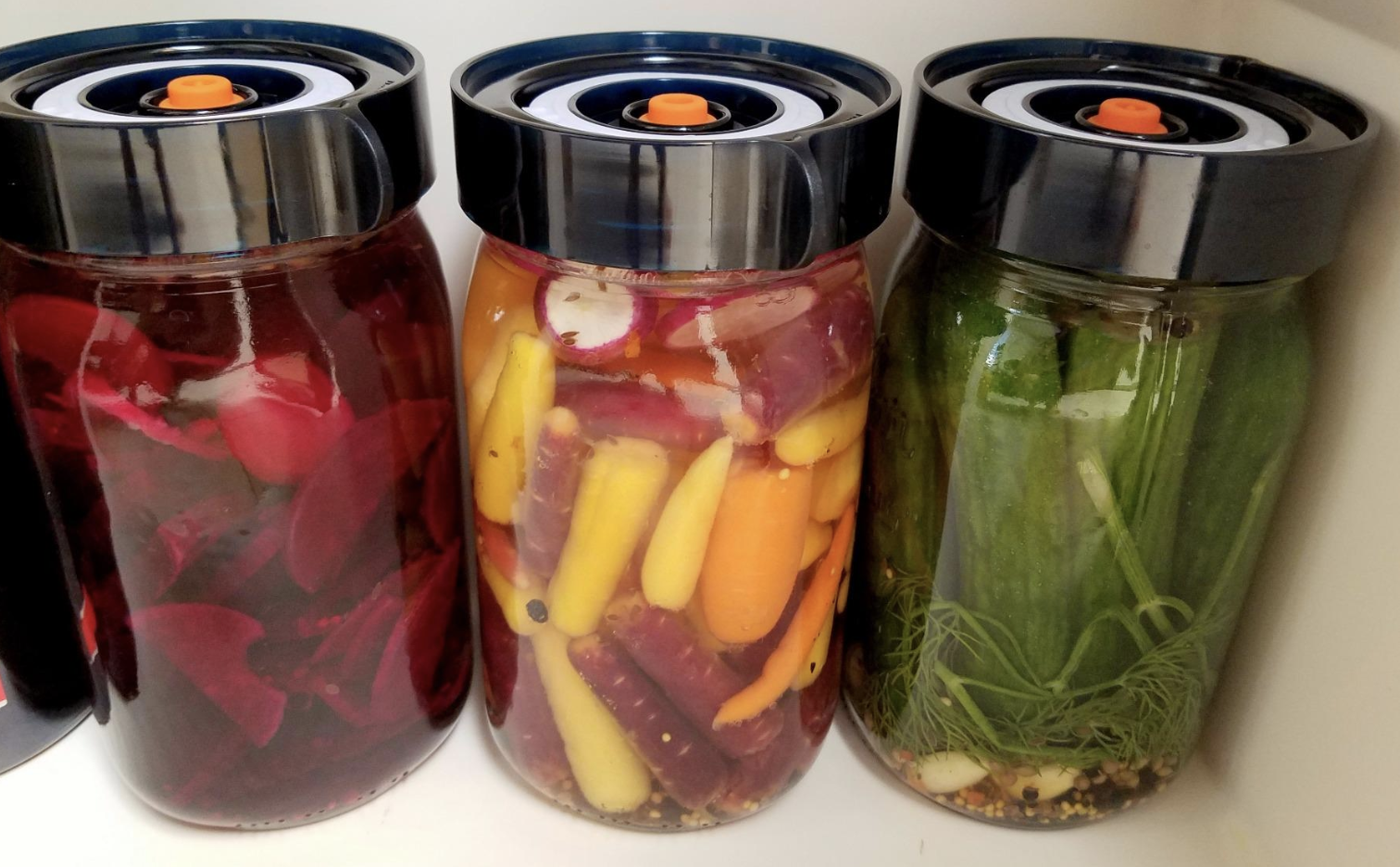 Three jars of fermenting beets, carrots, and cucumbers