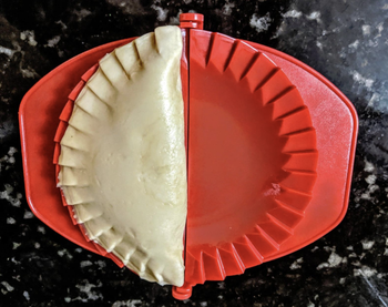An uncooked empanada in one of the dough presses after being shaped