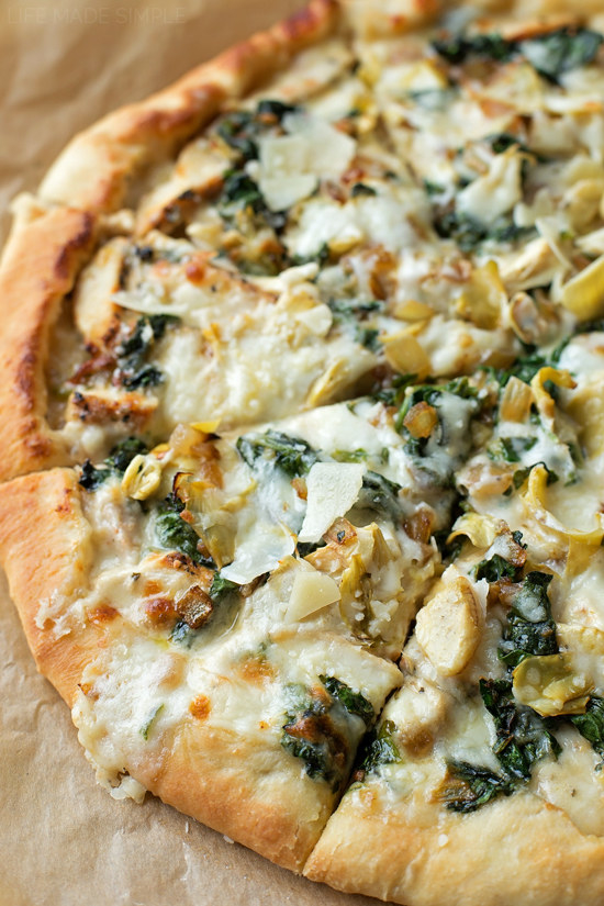 A pizza with spinach artichoke sauce cut into slices.