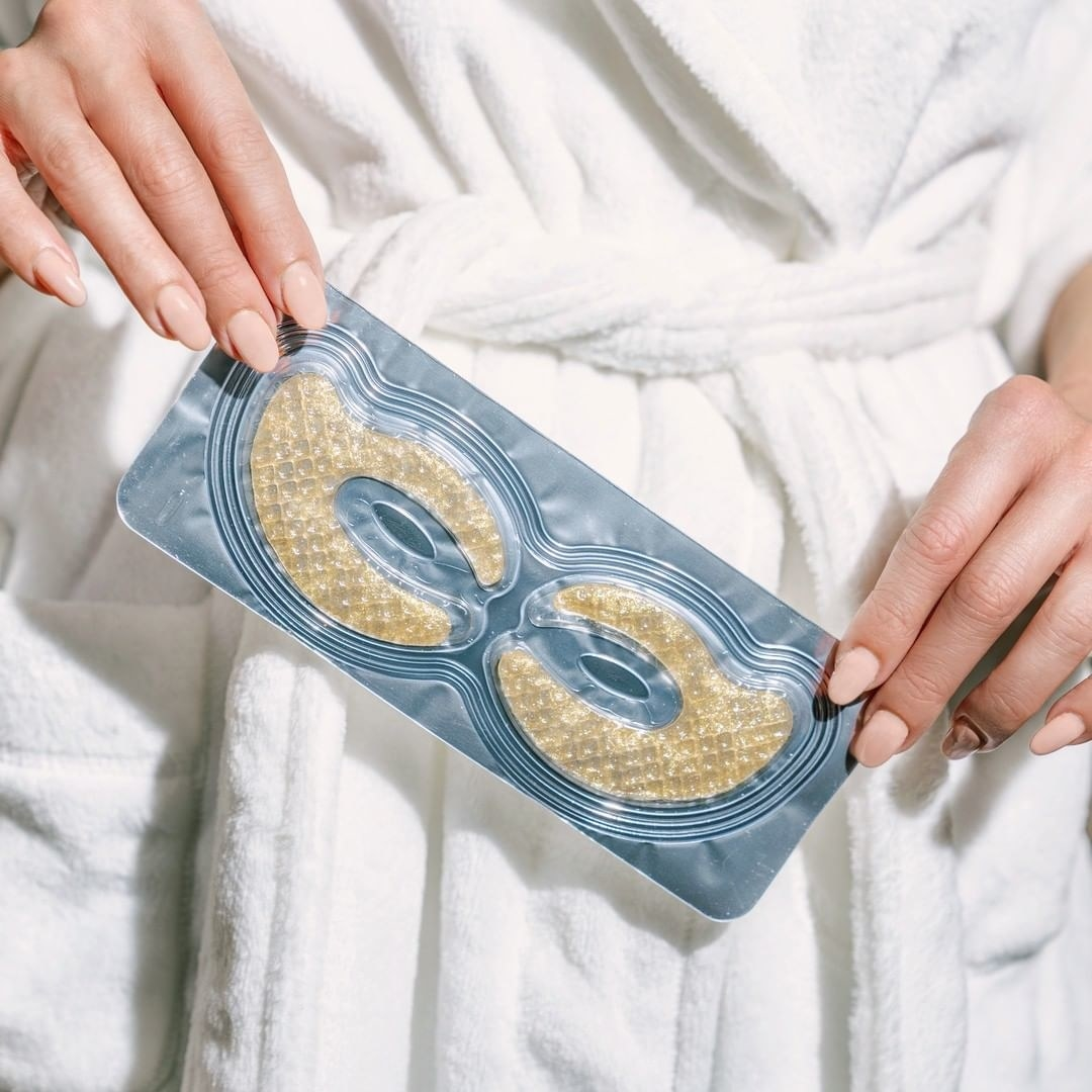 A person wearing a robe and holding a pack of gold eye masks