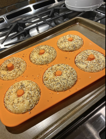 The silicone pan full of six fully baked everything bagels