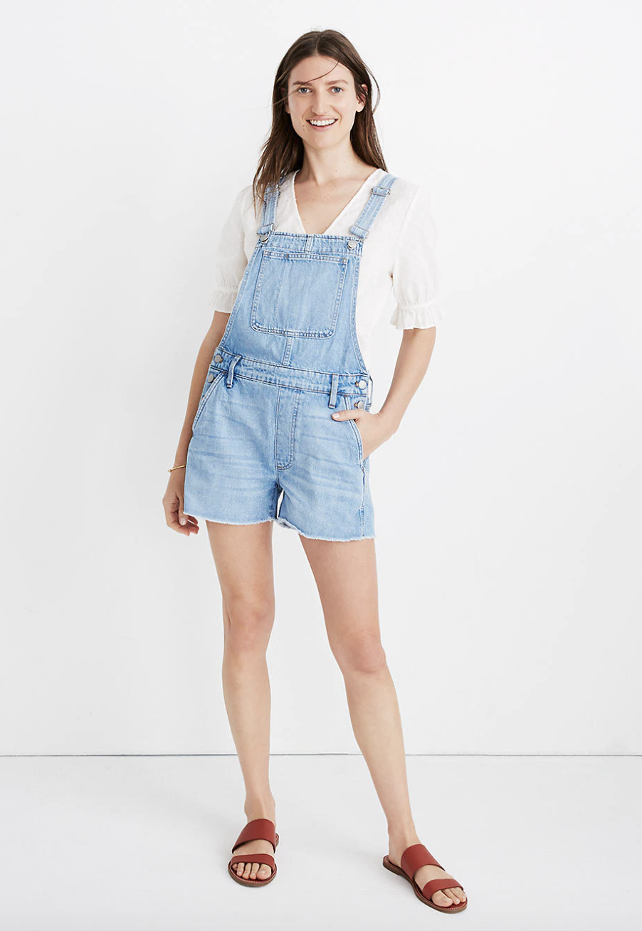 a model wearing the light blue denim short overalls