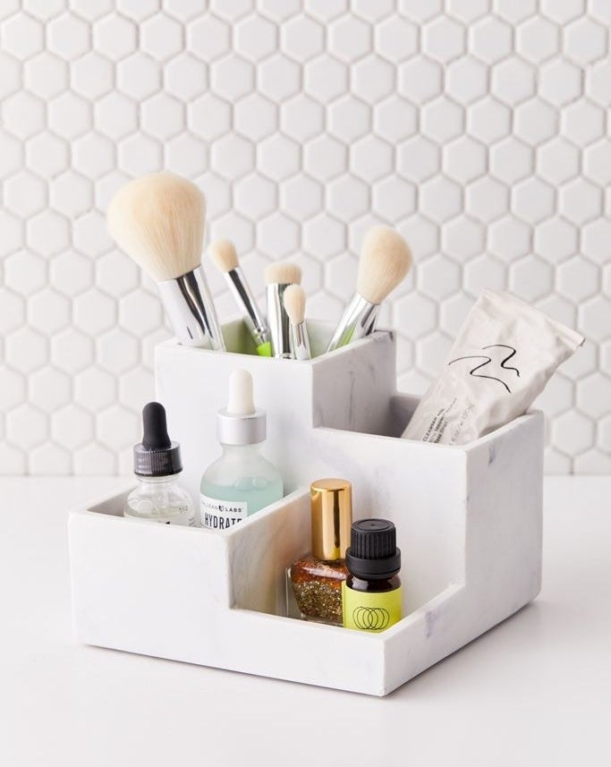 A cube tray with four square storage spots placed at different heights. One has room for brushes, another toothpaste, and the last two are large enough for nail polish and small serum bottles
