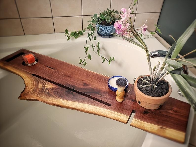 An Etsy shop owner's photograph of their wood caddy, with a slot for and iPad, a smartphone, and a cup holder. The wood is a flat piece that's long enough to extend past both sides of the tub.