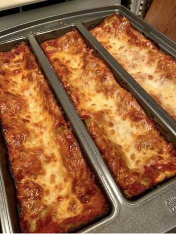 The pan with three rectangles of cooked lasagna in it