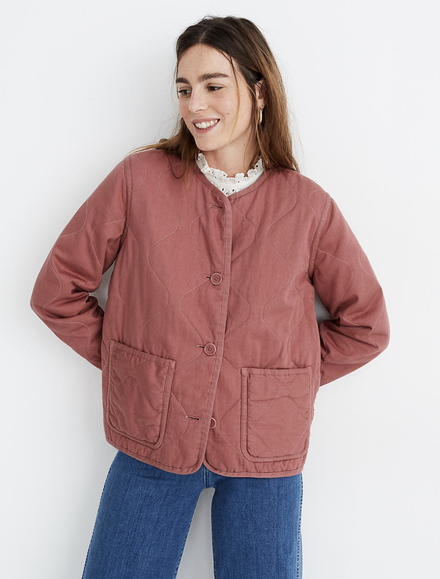 a model wearing a muted quartz quilted jacket with oversized front pickets and big buttons down the middle