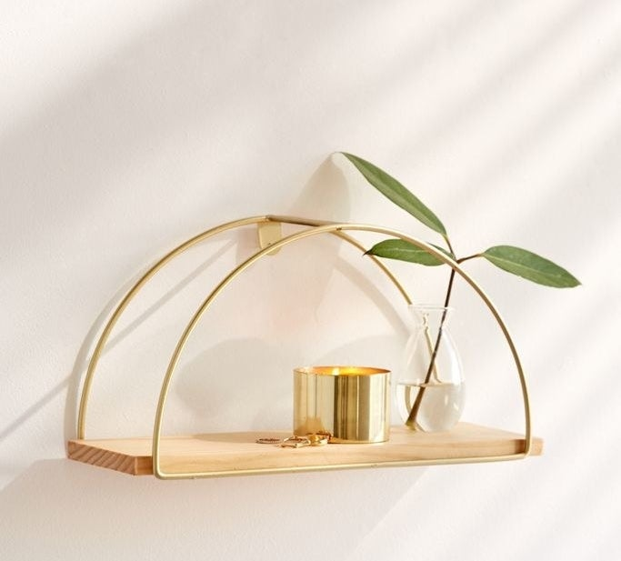 A lifestyle shot of the shelf, made with one piece of wood and two arched, metal decorative pieces, holding a candle, a few rings, and a small bottled plant